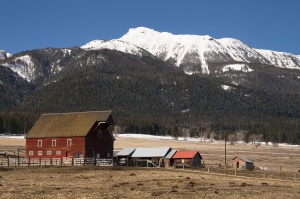 A red barn in early morning on the ranch against high mountain landscape